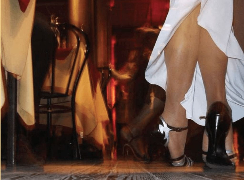 Photo taken from ground level of a woman dancer, from knees down, emphasizing her tango dance footwork. She is wearing a long white dress and black high heels--characteristic of a tango dancer. The floor is wood, and there are dining tables to the side of the dance floor.