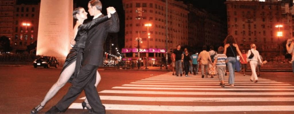 At 3 AM, in the crosswalk in Buenos Aires, a man and a woman dance the tango. Both are wearing formal black attire; she wears a black dress slit up to her upper thigh to show off her leg movement in the dance. Behind them, oridinary people cross the street.