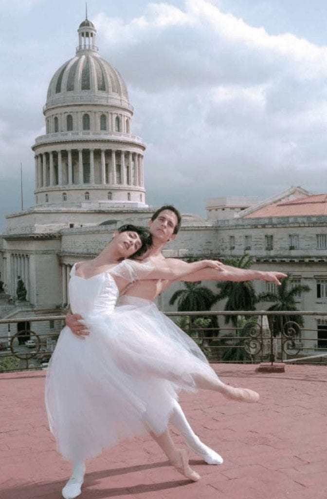 Two dancers, Lorna Feijóo and Nelson Madrigal, formerly of the Ballet Nacional de Cuba, pose in front of Havana's Capitolio. She wears a white chiffon dress, he wears white tights. In the photo, both face forward, his right hand on her stomach and left hand extended out, as he lifts her.