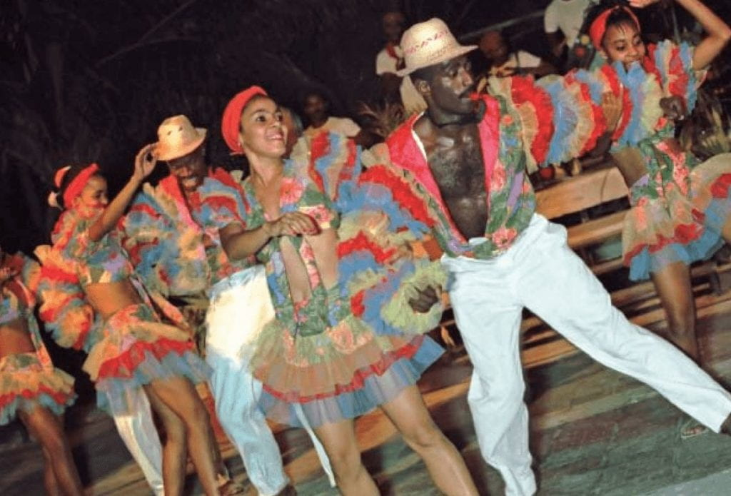 The banrrarra at the villa panamericana in Cojímar, Cuba, east of Havana, performs a Haitian-influenced carnival dance. Men and women dance in highly-colored outfits. The men wear white pants, with a colorful puffy shirt open to the waist. Men and women wear colorful puffy armsleeves.