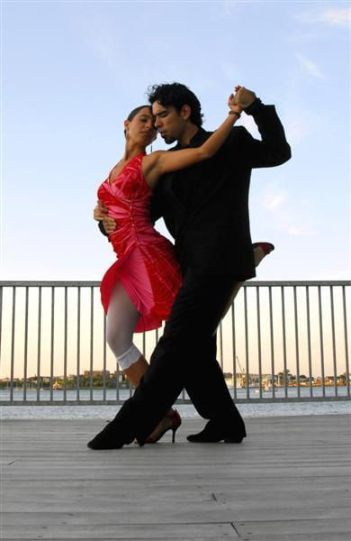 A man and a woman dance the tango on a dock. She wears a knee-length red dress, is is dressed in a black shirt, black pants, black coat. She is dancing in front of him (her back to his front) in a dance position known as
