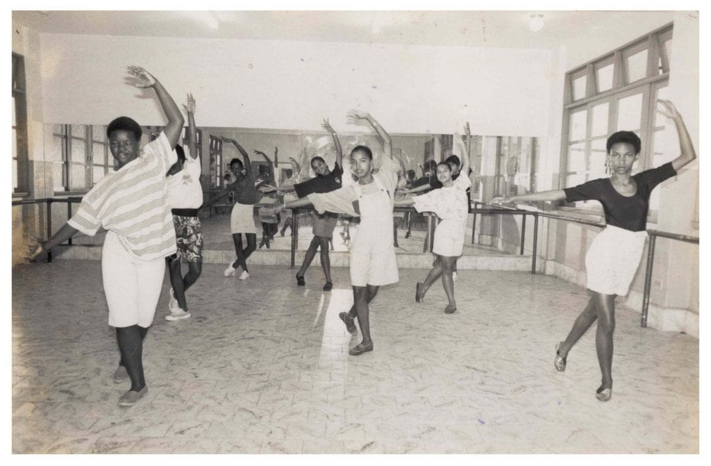 Photo of dancer and teacher Yolanda Demétrio as a work-student in Spain. Here she takes a dance class, in a studio with mirrors on the back wall and barres on all sides, along with seven other students.