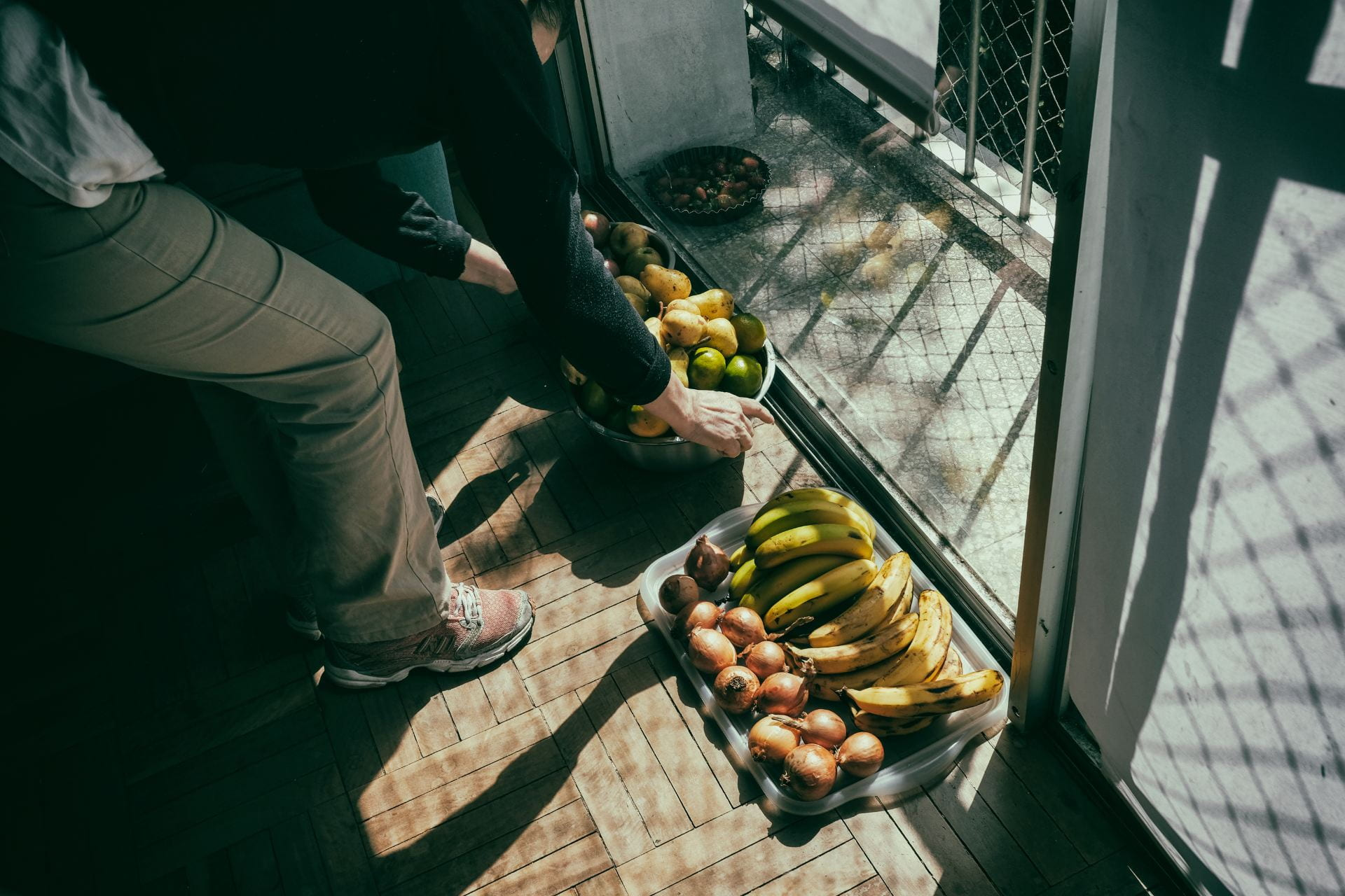 a person organizing the fruit on the floor