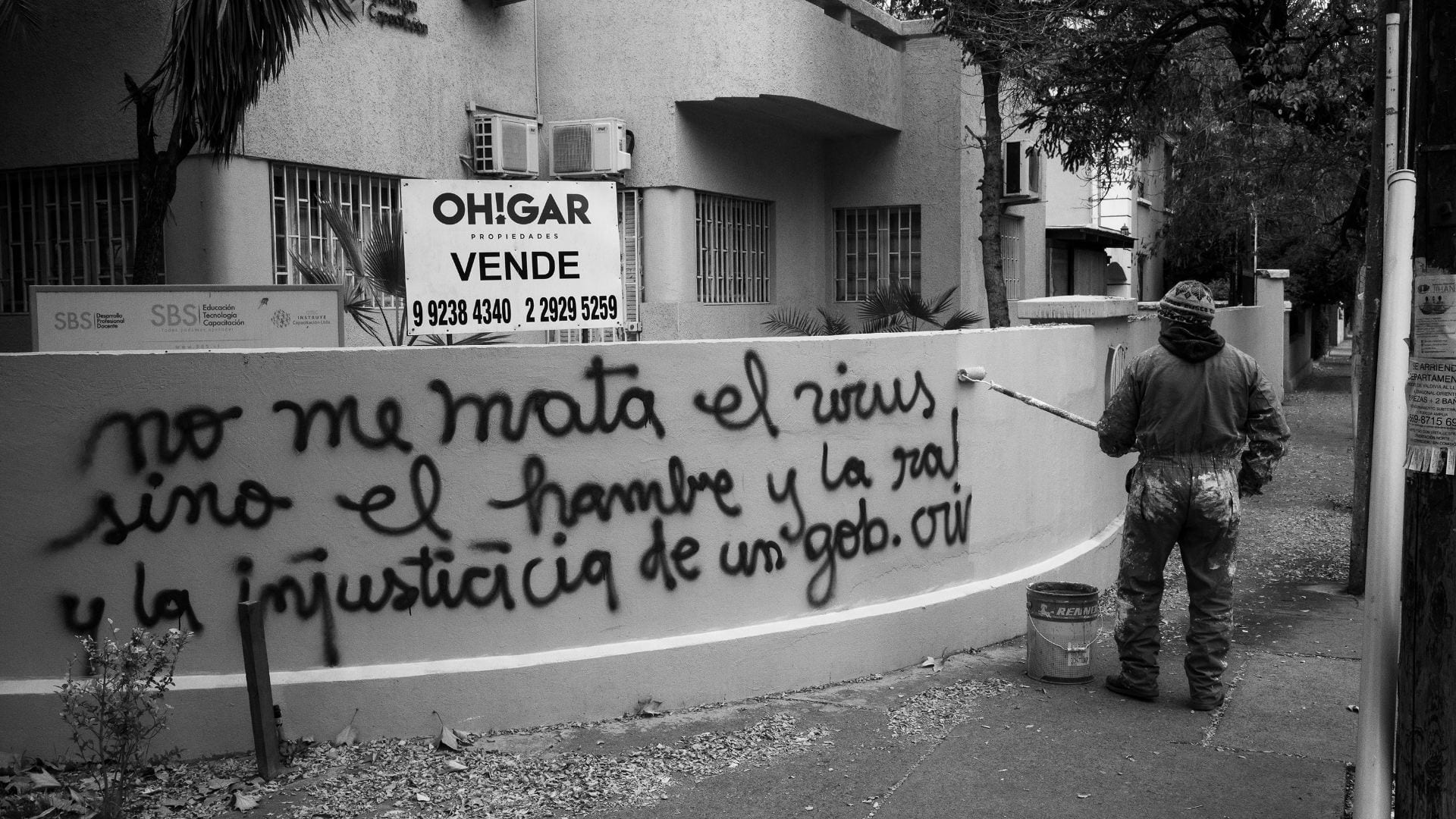 worker painting over graffiti that says: the virus is not killing me but hunger and injustice of a criminal government are