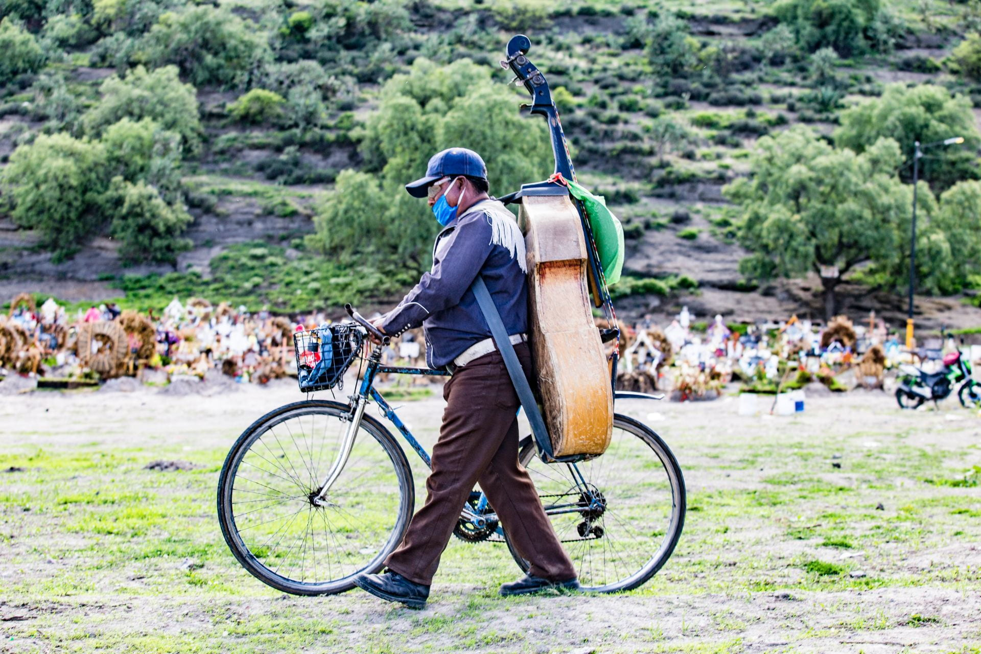 man with bicycle and musical instrument on his back