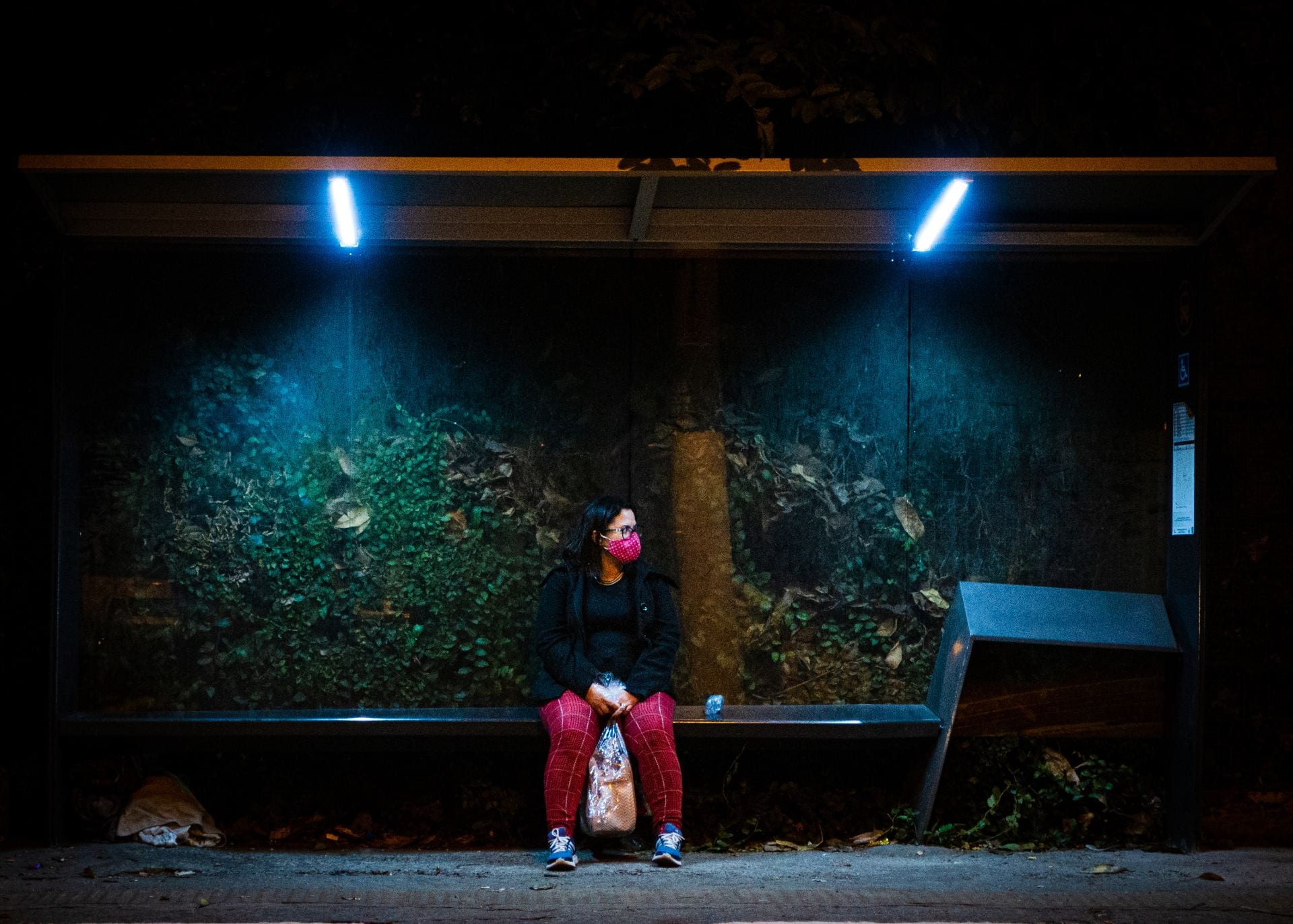 woman in red mask waiting for a bus