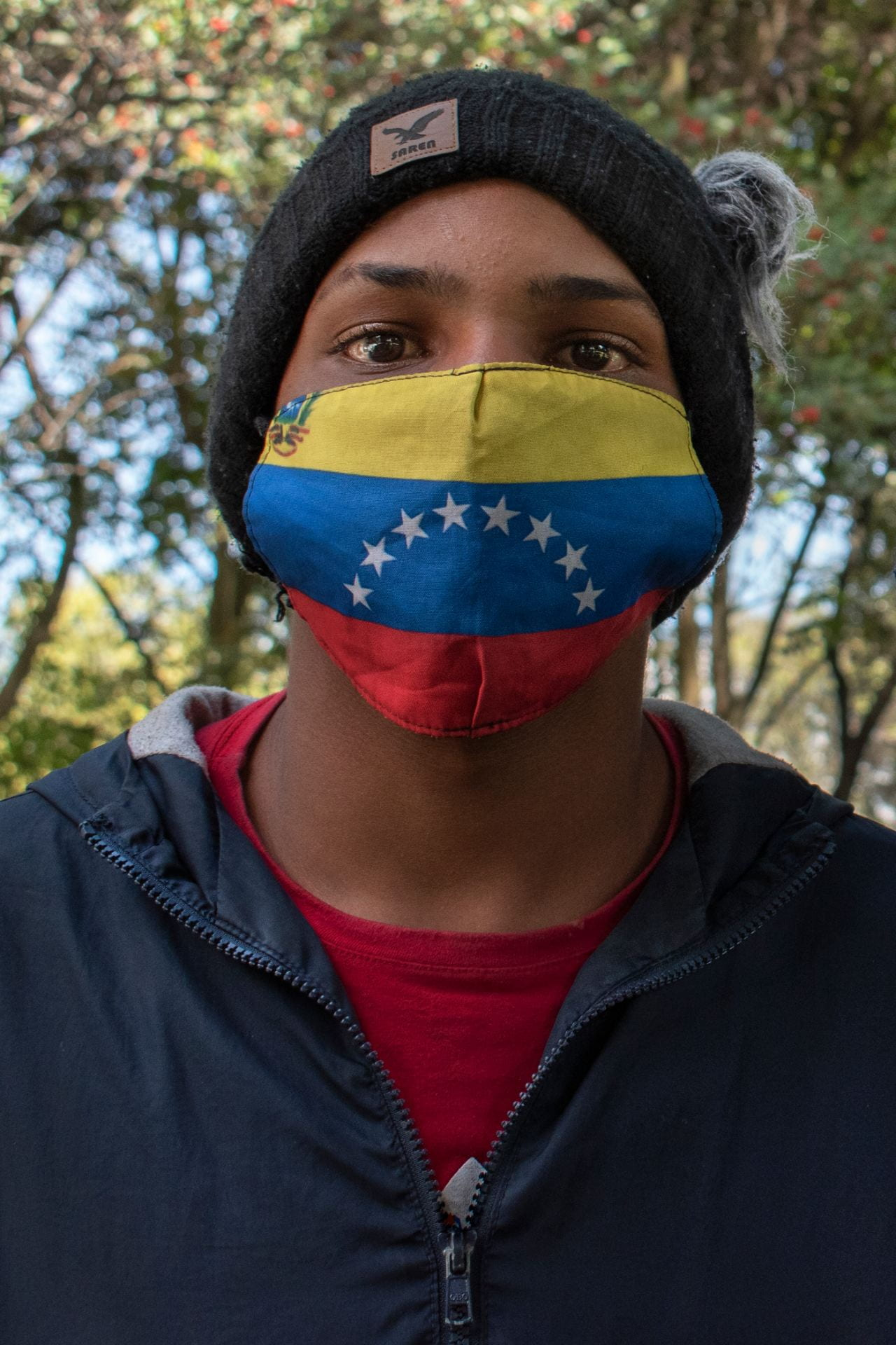 man with Venezuelan flag mask