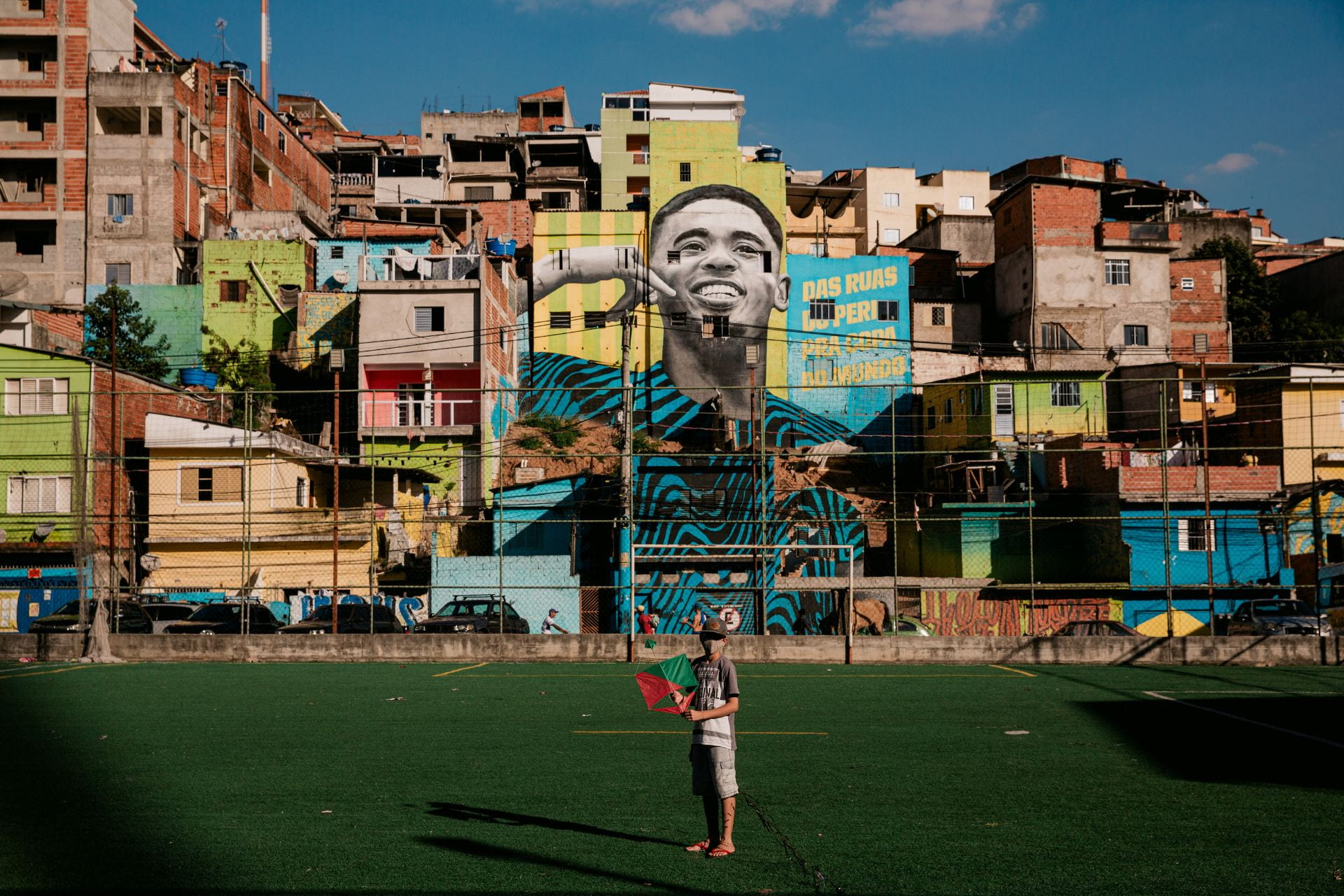 masked boy in sports field in front of murals