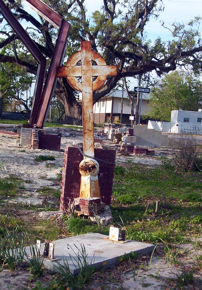 Rusty cross left standing in damages building site