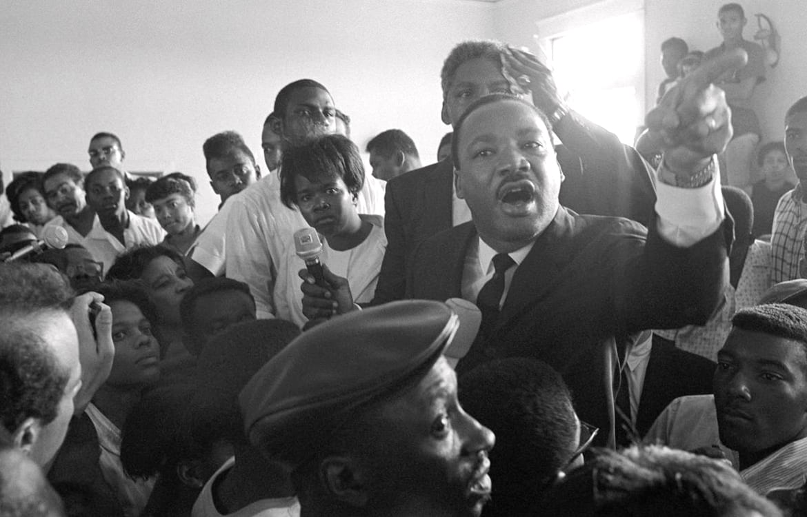 MLK speaking from the center of a crowd
