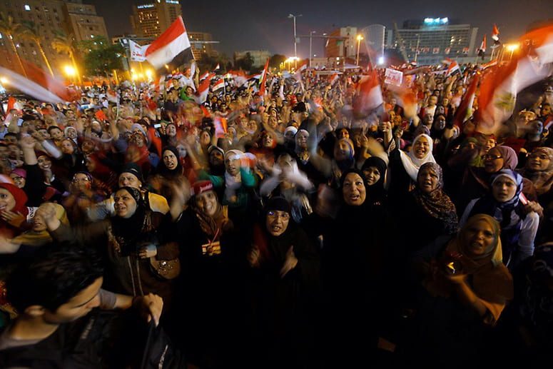 Protesters in Tahrir Square waving flags