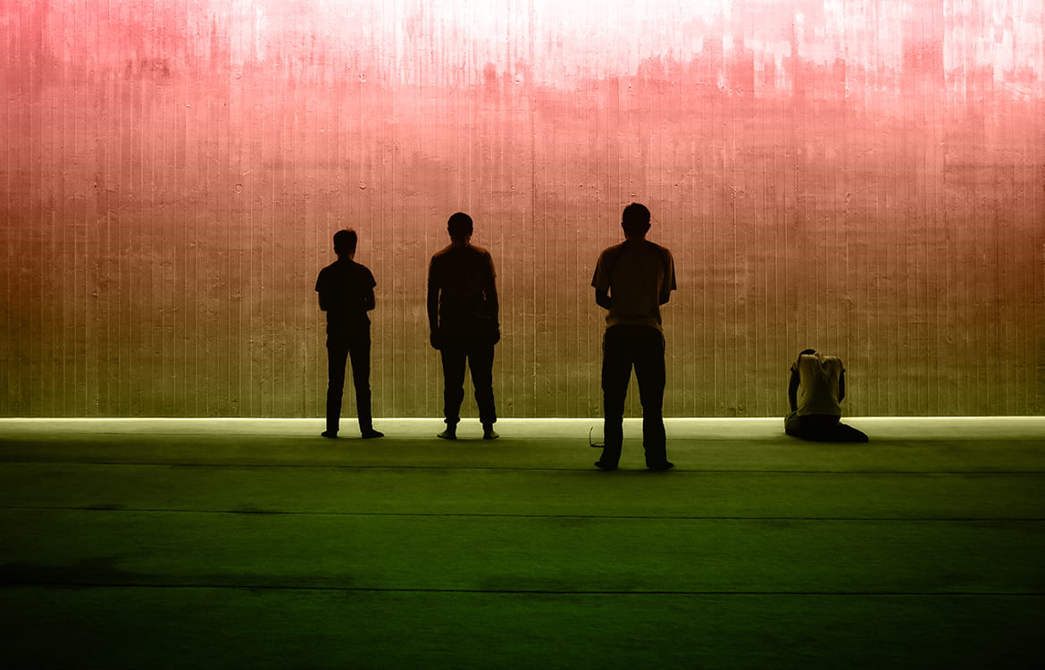 Silhouettes of three standing figures and on kneeling all seen with a muted color background