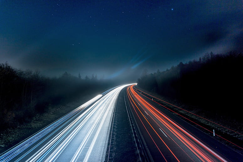 streams of light from cars on a highway photographed at a slow exposure