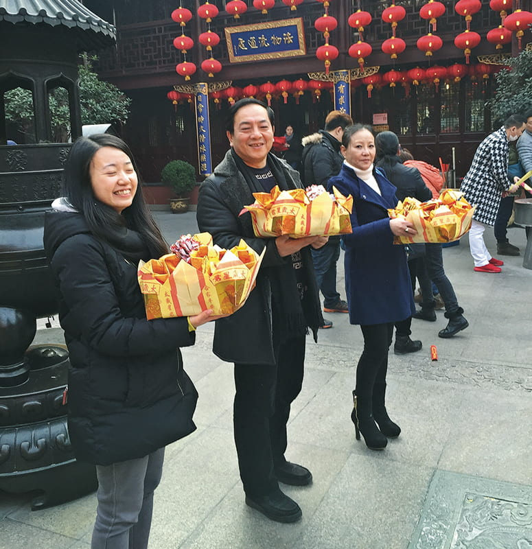Three people holding boxes of offerings in a Daoist temple