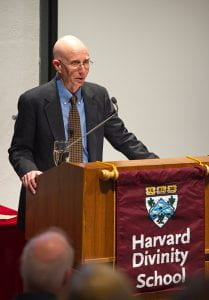 R. Gustav Niebuhr standing behind a podium with a Harvard Divinity School banner on it