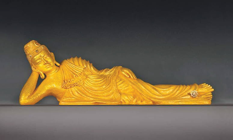 Gold figure of a reclining Buddha