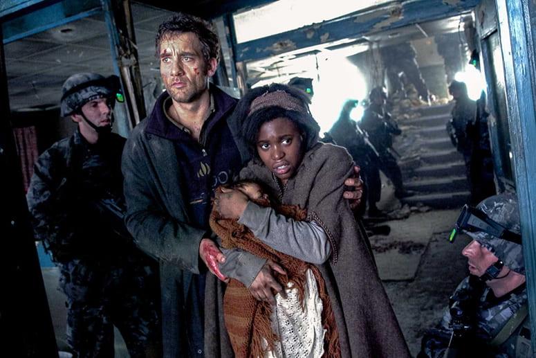 Film still of a man guiding a woman holding an infant through a broken down building