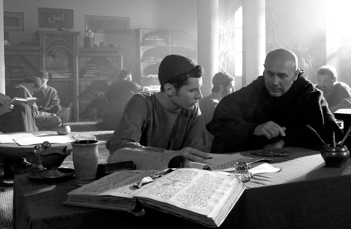 Men sitting in a library studying scrolls