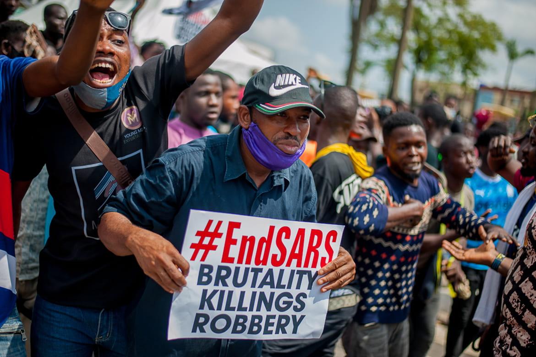 "Protestors holding signs ""#endSARS Brutality Killings Robbery"