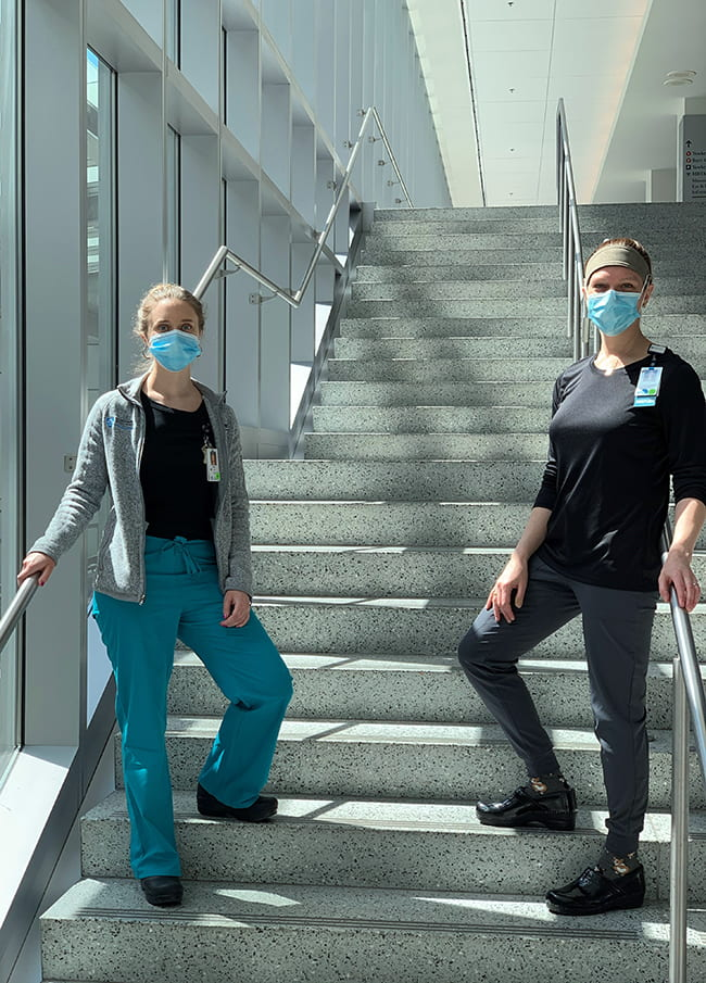 Two women dressed in scrubs, on the steps inside a hospital