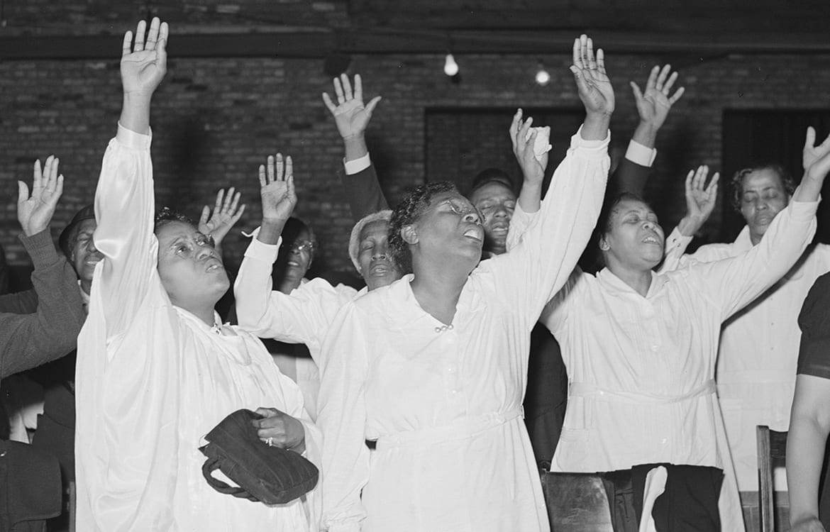 Pnetecostal women with their hands raised in praise fo the Lord during a worship service
