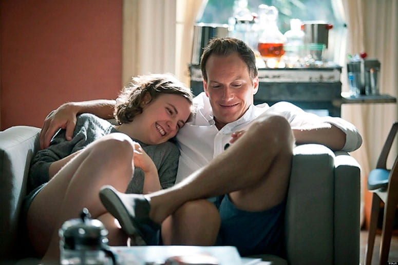 Film still from Girls of a happy couple snuggling on a couch reading