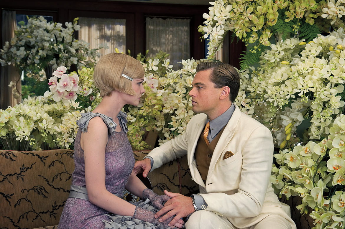 Film still from Gatsby with a 1920s male and female couple seated on a garden bench, gazing at each other