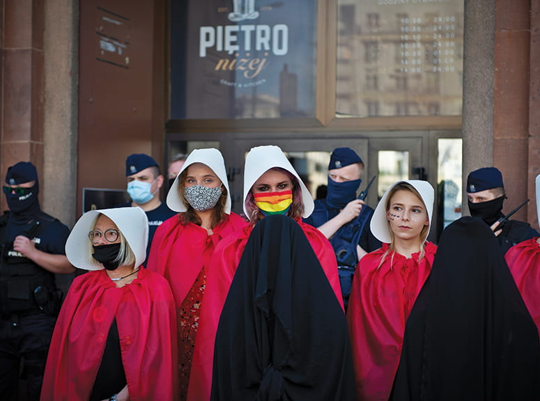 Women wearing red robes and white dutch bonnets, masked against covid-19, standing in line wiht police visible behind them