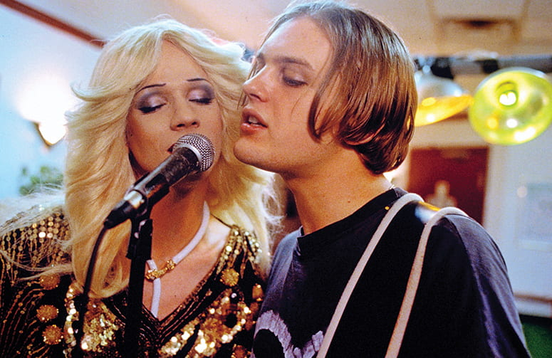 Film still of two singers together at a microphone