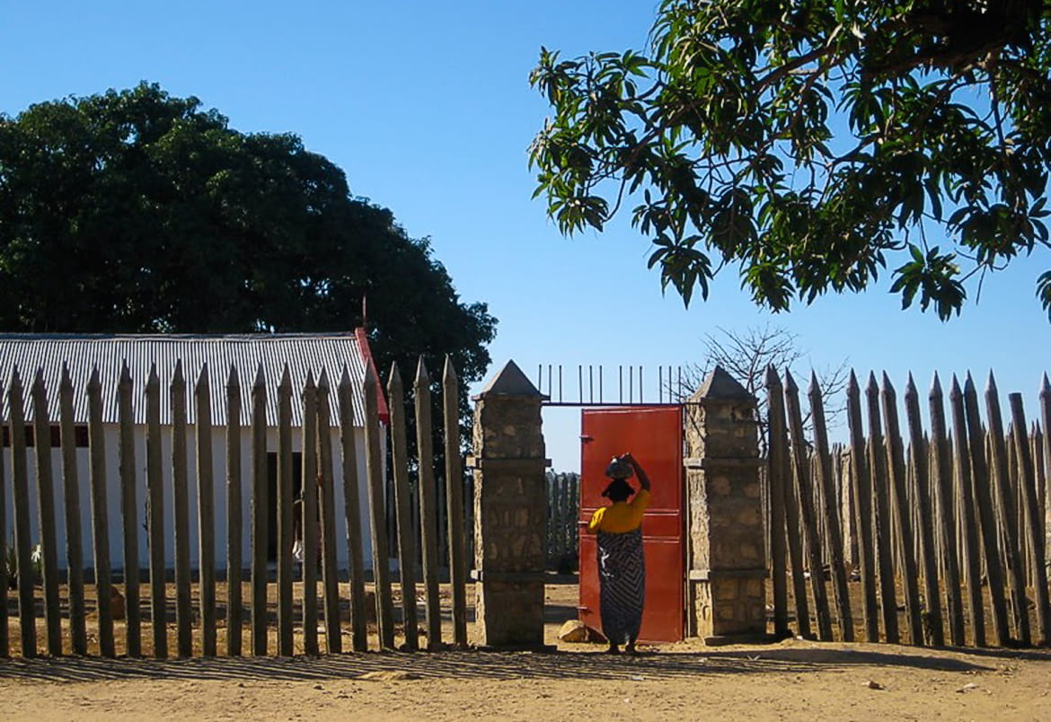 Photo of an African woman at the gate of a village surrounded by a loose wooden fence