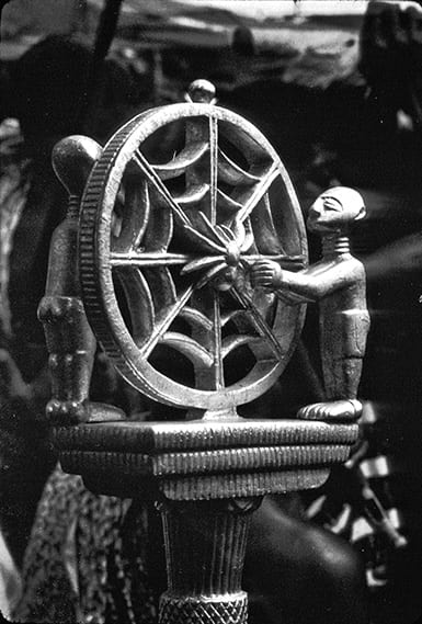 The top of a wooden divination staff carved as two figures next to a spider web with a spider in the center