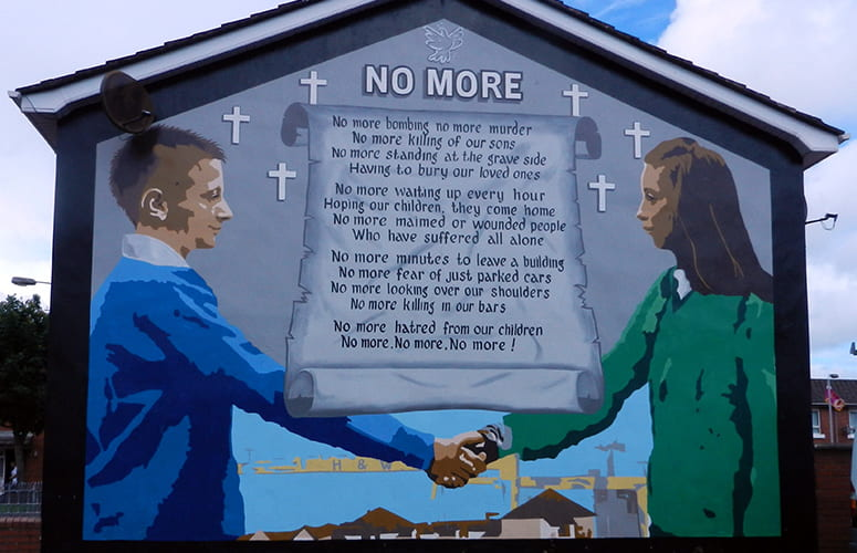 Mural showing a boy and girl shaking hands with the text of a poem titled No More behind them