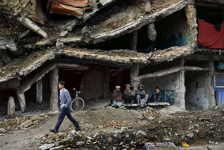 Photo of four Afghani men sitting in the ruined shell of a building while another man walks past, on the rubble-covered street