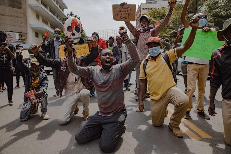 Kneeling protestors holding signs chanting