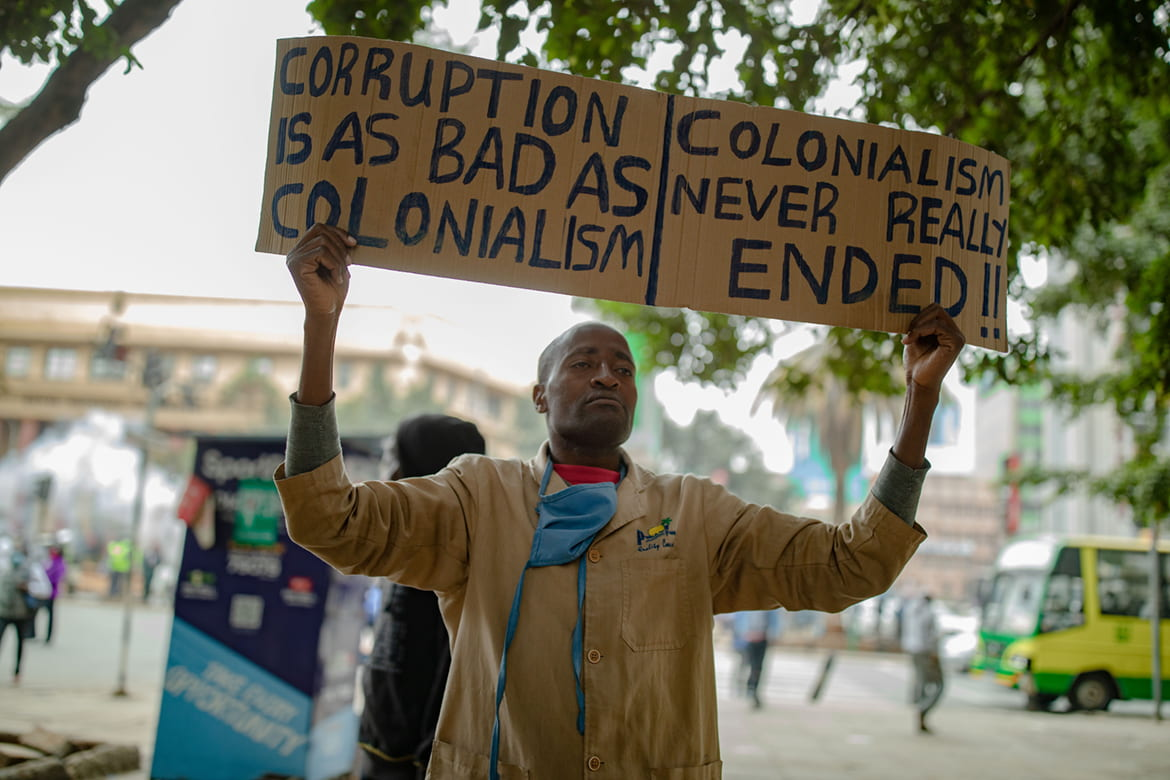 Man holding a protest sign reading Corruptions is as bad as colonialism. Colonialism never really ended.