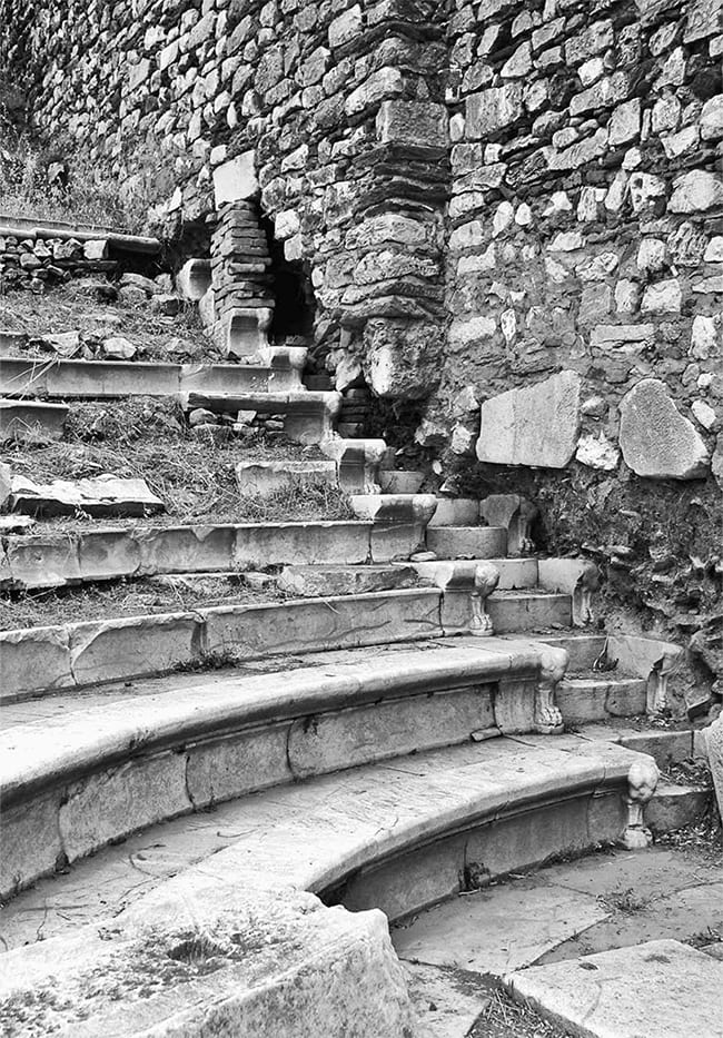 Black and white photo of crumbling stone steps with grass growing among the stones