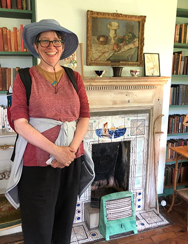 Paulsell standing in front of a fireplace