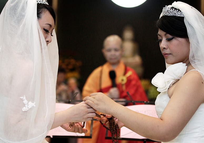Photo of two brides, with Buddhist nun Chao-hwei in the background, presiding over the wedding ceremony