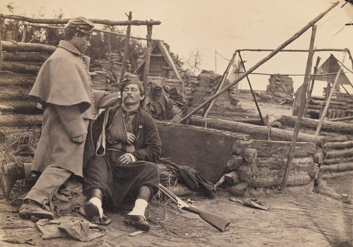 Historic photo of civil two war soldiers, one sitting on the ground with his arm in a sling