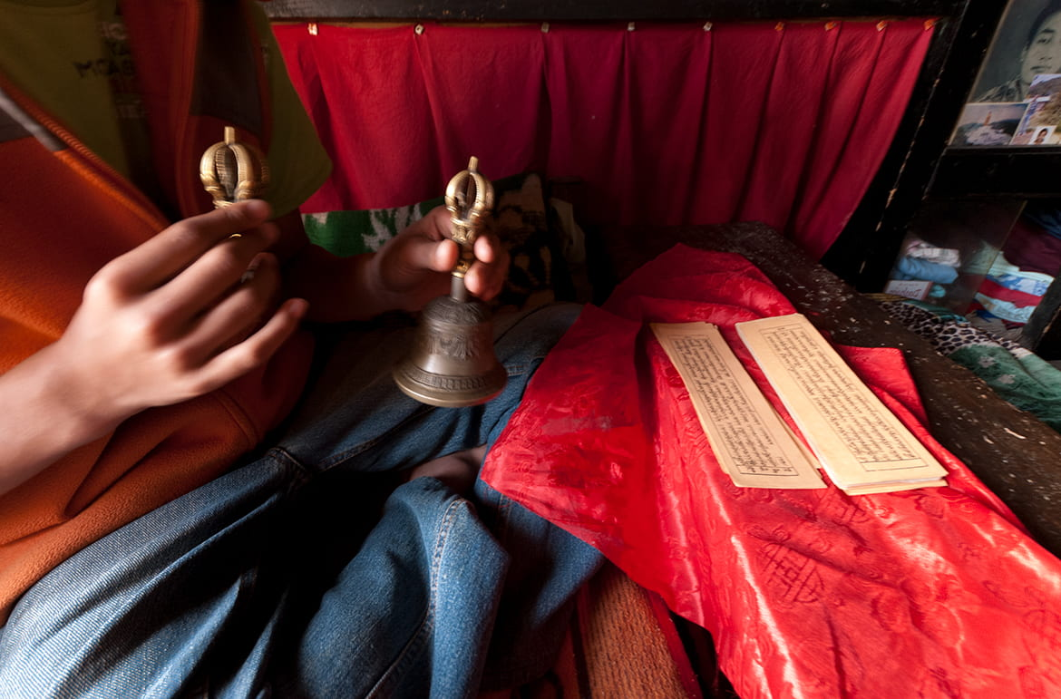 Practitioner holding prayer bells with Buddhist scripture in front of him