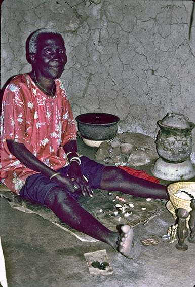 Photo of a seated woman surrounded by her tools of divination