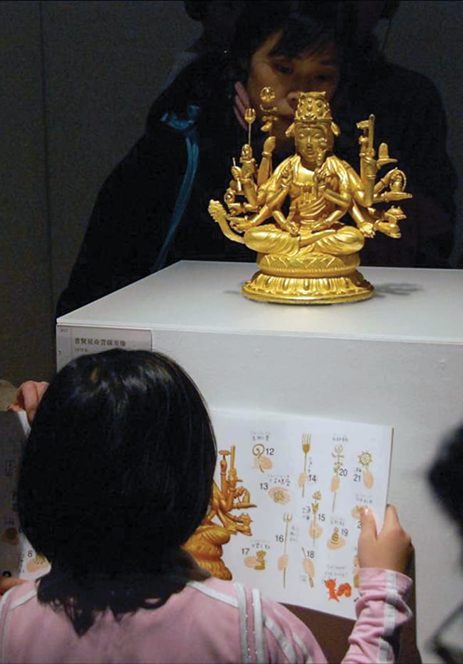Young girl looking at a Buddhist figurine in a museum display