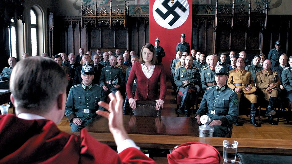 Woman standing in a courtroom full of soldiers with a Nazi flag hanging in the back