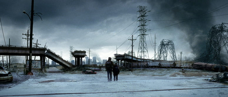 Film still from The Road with two figures walking through through an apocalyptic landscape