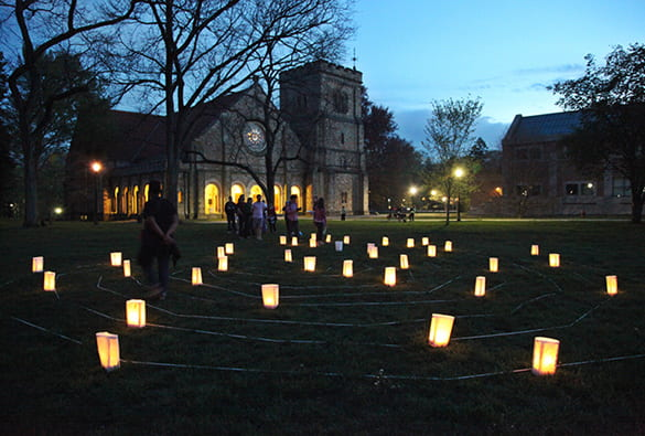 Photo of luminary lights on a campus green with students