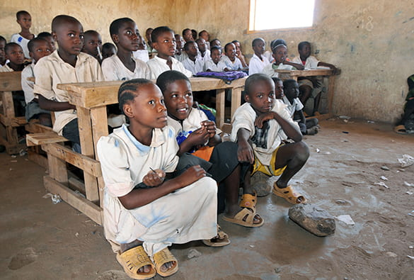 Children in a refugee camp schoolroom in Africa, some at desks some on the dirt floor