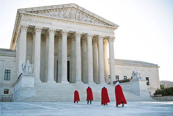 Photo of four women wearing red robes walking to the steps of the US Supreme Court building