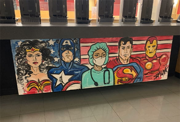 Mural of superheroes Wonder Woman, Captain America, Superman, and the Flash, with a person in scrubs in the middle
