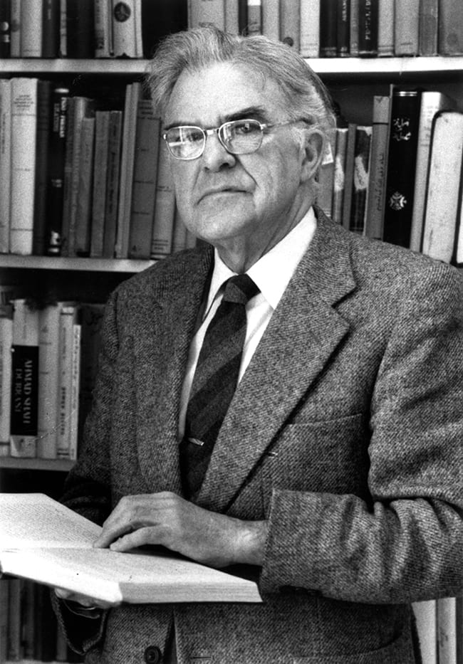 photo of Wilfred Cantwell Smith holding a book in his office