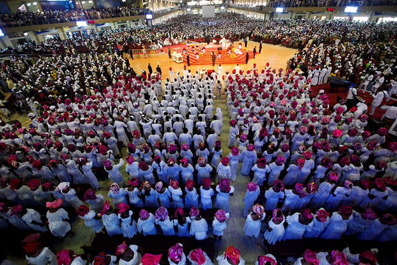 Photo of a congregation of thousands of people worshipping in a Nigerian megachurch